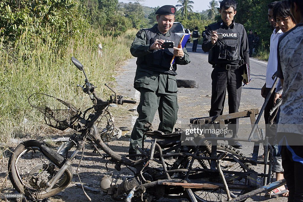 Thai bomb squad members inspect the site of a roadside bomb attack by suspected separatist militants on a pick-up truck carrying rangers in Thailand's restive southern province of Pattani on March 30, 2013. Two rangers were killed and four wounded when the bomb placed in a motorcycle detonated as the pick-up truck passed by. A stubborn insurgency seeking greater autonomy has raged across several provinces in the south of Thailand bordering Malaysia for nine years -- with near-daily shootings and bombings. AFP PHOTO/Tuwaedaniya MERINGING