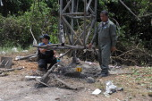 Thai bomb squad members inspect the site of a roadside bomb attack on a police vehicle in the Chanae district of Thailand's restive southern province...