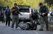 Thai bomb squad members inspect the site of a roadside bomb blast planted by suspected separatist militants in the Choirong district of Thailand's...