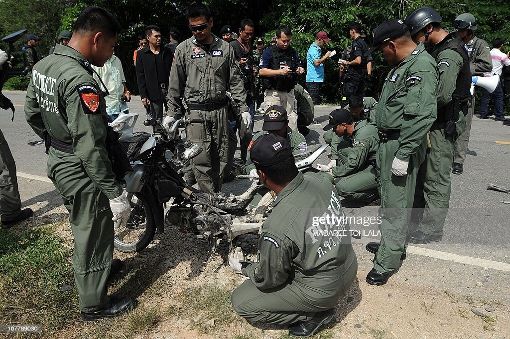 Thai bomb squad members inspect the wreckage of a motorcycle following a roadside motorcycle bomb blast targeting a patroling police pick-up truck triggered by suspected separatist militants in the Ra-ngea district of Thailand's restive southern province of Narathiwat on April 30, 2013. More than 5,500 people have been killed in Thailand's Muslim-majority south since 2004, with shadowy insurgent groups blamed for near-daily bombings and shootings. AFP PHOTO/Madaree TOHLALA