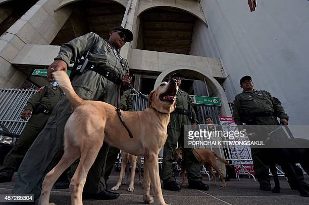 Thai bomb squad units and sniffer dogs carry out security checks at the venue entrance prior to play between Thailand and Iraq during the football...
