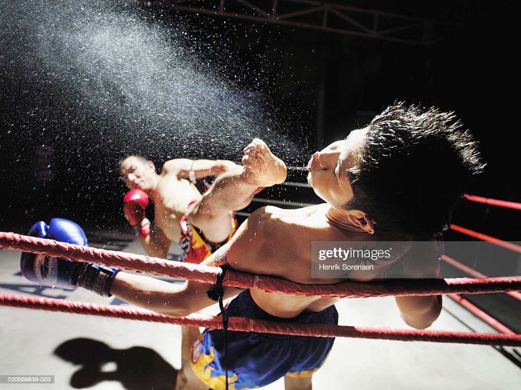 Thai boxing match, one boxer kicking another in face : Stock Photo