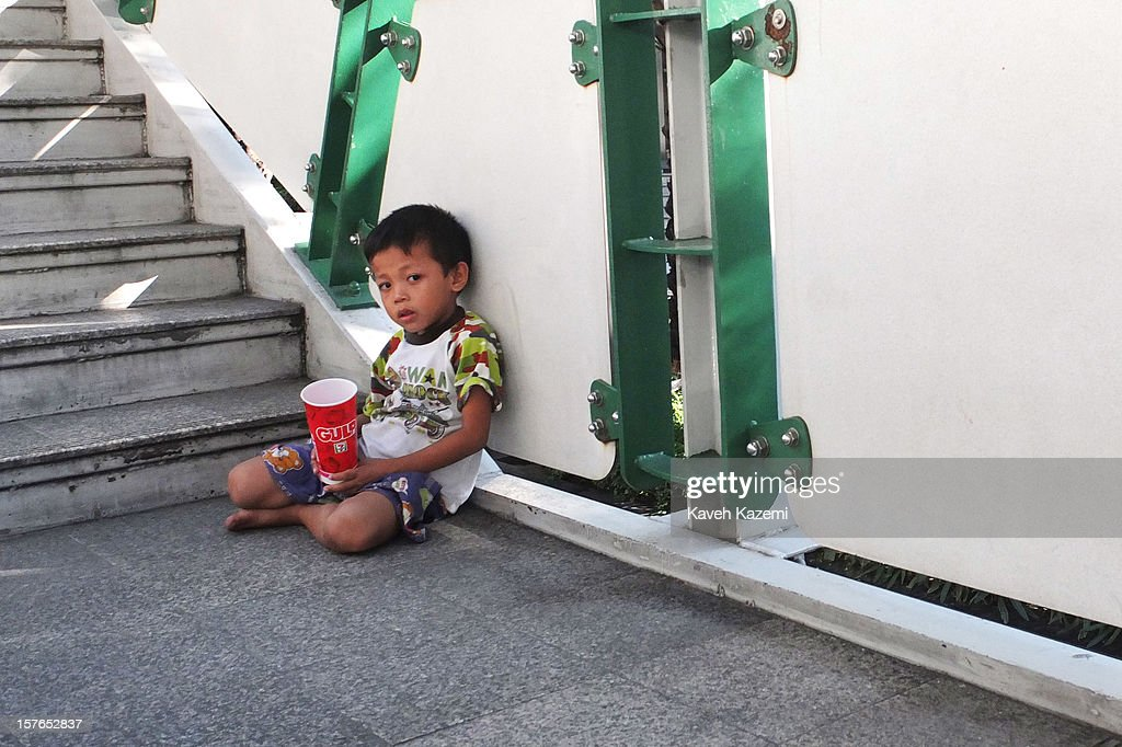 A Thai boy begs with a softdrink cup in his hand while sat on the stairway of sky train station on October 25, 2012 in Bangkok, Thailand.