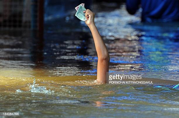 A Thai boy holds aloft banknotes to keep them dry while he swims during the flood in Nonthaburi province suburban Bangkok on October 15 2011 Thailand...