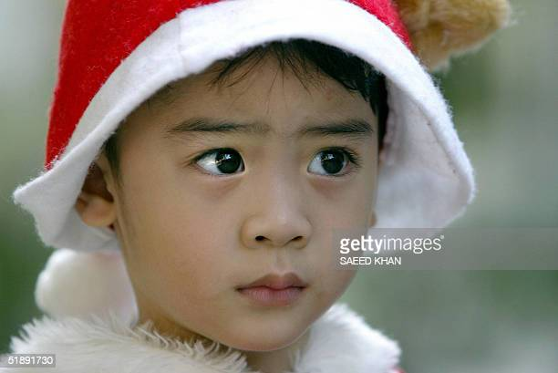 Thai boy wearing a Santa Claus hat watches a elephant performance aimed at entertaining school children in Ayuttaya some 80 kilometers north of...