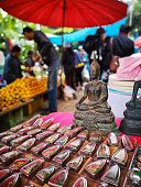 Thai Buddha amulets and Buddha images for sale at a local general Northern Thai market in Chiang Mai Province, people can be seen out of focus in the background purchasing fresh fruit. Thailand.