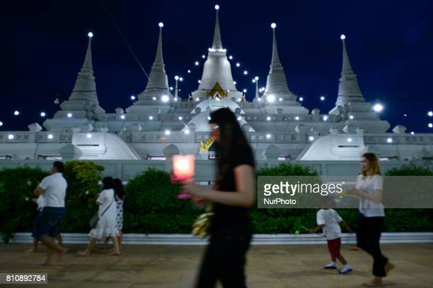 Thai Buddhist hold candles and incense they perform during a ceremony marking Asalha Puja Day in Wat Asokaram Samut Prakan Thailand 8 July 2017...