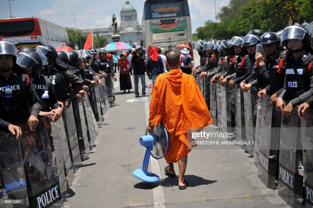 A Thai Buddhist monk carries a fan past lines of policemen as he leaves the site of an anti-government rally at the premier's office, in Bangkok on April 14, 2009. Thai anti-government protesters threatened with a military offensive abandoned a three-week rally at the premier's office, pulling the kingdom back from a potentially bloody showdown in the streets. AFP PHOTO/Christophe ARCHAMBAULT