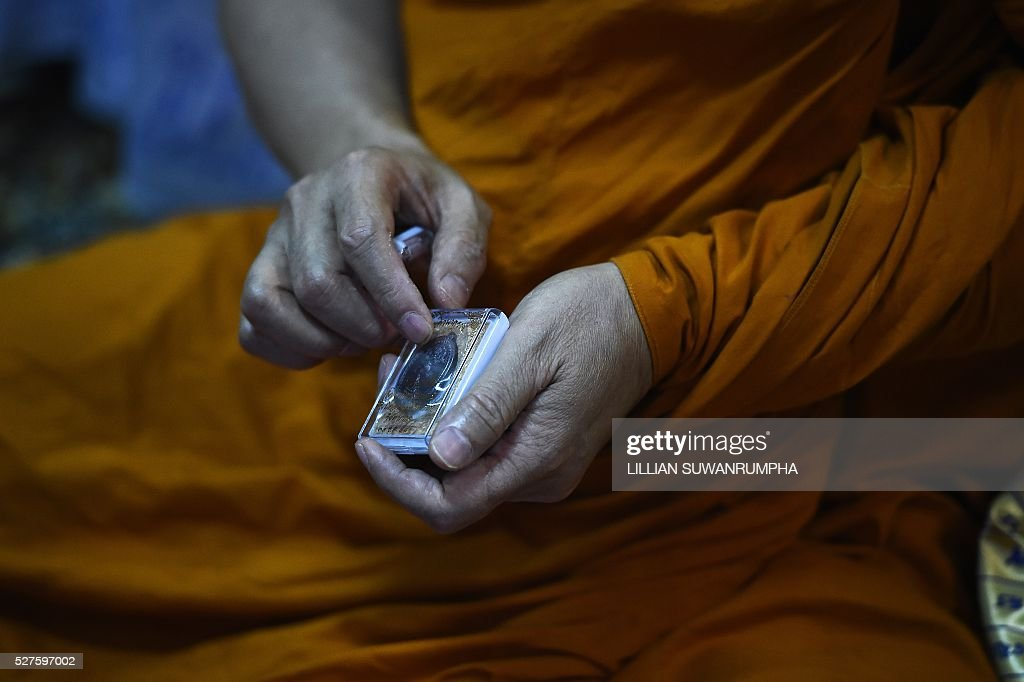 Thai Buddhist monk Phra Prommangkalachan, who had blessed Leicester City football players, shows one of the new amulets that Leicester players will soon receive during a press conference at the Traimitr Withayaram Woraviharn Temple in Bangkok on May 3, 2016. The Buddhist monk who has blessed Leicester City's players and stadium said he prayed deep into the night as the Foxes pulled off one of the biggest ever sporting shocks by winning the English Premier League. Phra Prommangkalachan, who has travelled to the Midlands club several times with its billionaire Thai owner, said he was praying during second-placed Tottenham Hotspur's 2-2 draw at Chelsea, which gave Leicester the title. / AFP / LILLIAN