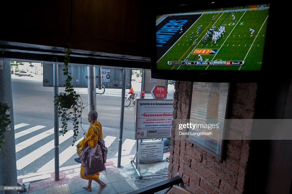 Thai Buddhist monk walks past a pub where ex-patriots and others gathered to watch Superbowl 50. The Denver Broncos defeated the Carolina Panthers 16-10 to win the football championship. The game was played in San Francisco and championship has been a part of American history since 1967.