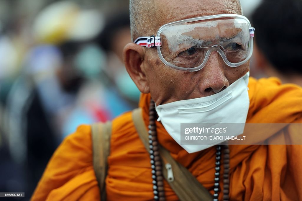 A Thai Buddhist monk wears glasses and a mask as protection against tear gas during an anti-government protest in Bangkok on November 24, 2012. Thai police on November 24 fired tear gas and detained dozens of demonstrators as clashes erupted at the first major street protests against Prime Minister Yingluck Shinawatra's government. AFP PHOTO/Christophe ARCHAMBAULT