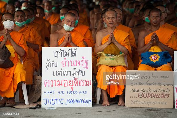Thai Buddhist monks from the Dhammakaya Temple covered their faces while chanting during a confrontation with police officers outside the temple in...