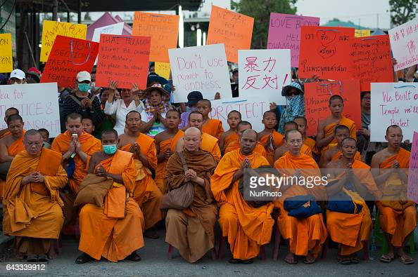 Thai Buddhist monks outside the Dhammakaya Temple while chanting during a confrontation with police officers outside the temple in Pathum Thani...
