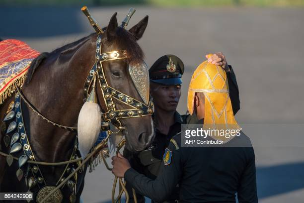 A Thai cadet helps to adjust the special ceremony headgear for a fellow cadet as they stand next to a horse near the Grand Palace before a dress...