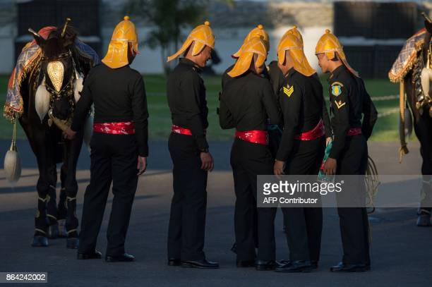 Thai cadets wearing special ceremony uniforms stand next to a horse as they view a group photo they took near the Grand Palace before a dress...