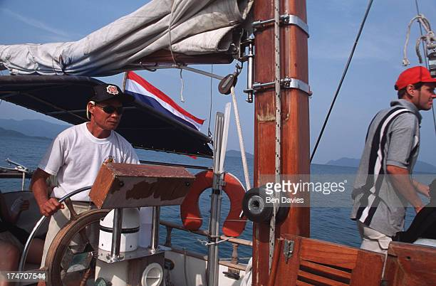 Thai captain steers a luxury tourist yacht through the islands of the Koh Chang National Marine Park in the Gulf of Thailand The park is made up of...