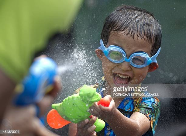 A Thai child takes part in water battles to celebrate Songkran Festival for the Thai New Year at Khao San road in Bangkok on April 12 2014 Songkran...