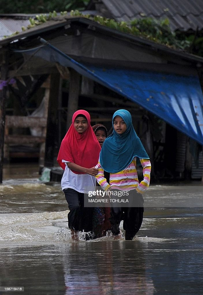 Thai children walk through flood waters after flash floods hit partsThailand's restive southern province of Narathiwat on December 26, 2012. Southern provinces of Thailand have been hit by floods over the past few days, with tens of thousands of residents affected.