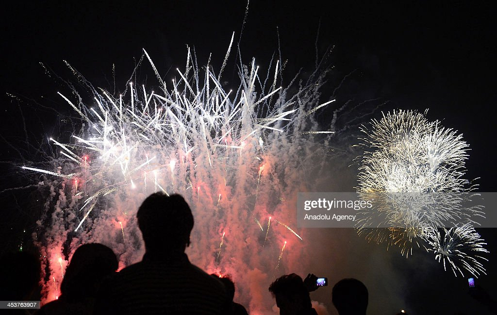 Thai citizens take a picture of fireworks at Sanam Luang to celebrate the 86th birthday of King Bhumibol Adulyadej on December 5, 2013 in Bangkok, Thailand.