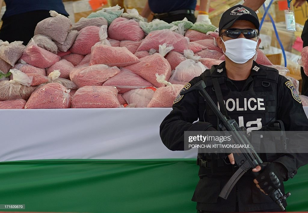 Thai commando unit stand guard in front of packs confiscated narcotics before destroying them marking the UN's International Day Against Drug Abuse and Illicit Trafficking in Ayutthaya province on June 26, 2013. More than 3363 kilograms of confiscated narcotics including methaphetamine, heroin, opium, cocaine and psychotropic substances with an estimated value of 10 billion bahts (324 million USD) were to be burnt.
