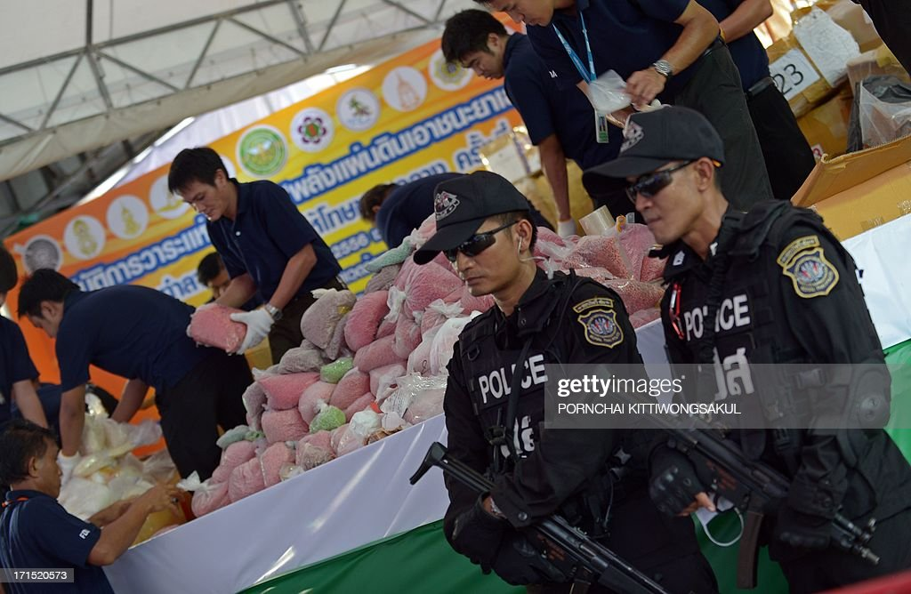 A Thai commando unit stand guard in front of packs confiscated narcotics before destroying them marking the UN's International Day Against Drug Abuse and Illicit Trafficking in Ayutthaya province on June 26, 2013. More than 3363 kilograms of confiscated narcotics including methaphetamine, heroin, opium, cocaine and psychotropic substances with an estimated value of 10 billion bahts (324 million USD) were to be burnt.