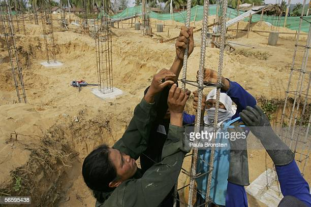 Thai construction workers help construct the foundation on a site for a new hotel along the beach January 13 2006 in Khao Lak Thailand Over a year...