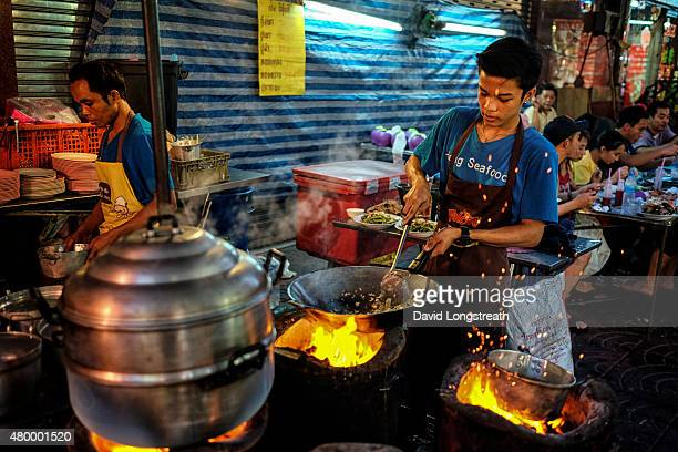 Thai cook prepares food at a street kitchen in Chinatown Thailand is known for its wide variety of street food and very popular with both local...