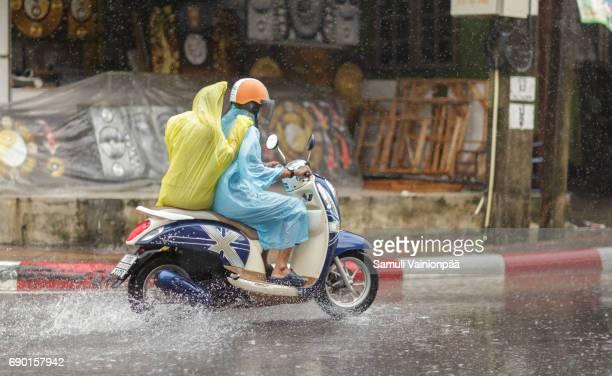 Thai couple ride through monsoon rain