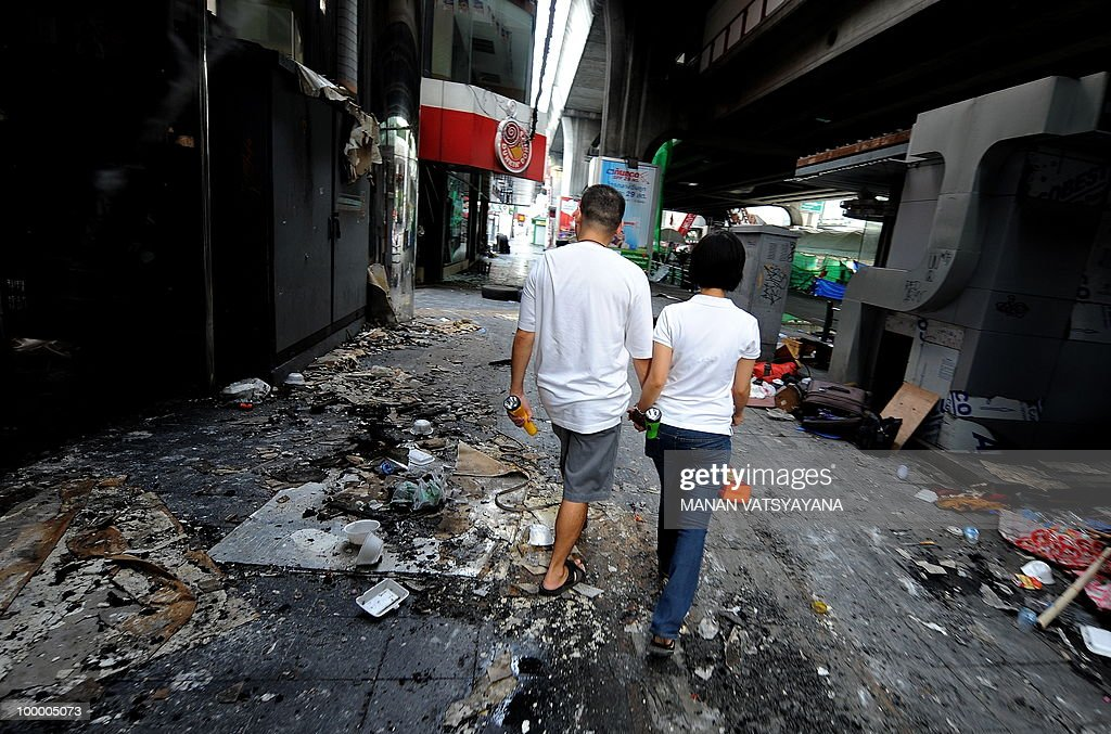 A Thai couple walks past burnt shops in downtown Bangkok on May 20, 2010. Thai police escorted thousands of protesters out of a Buddhist temple where they had cowered overnight after nine people were killed there in gunbattles.
