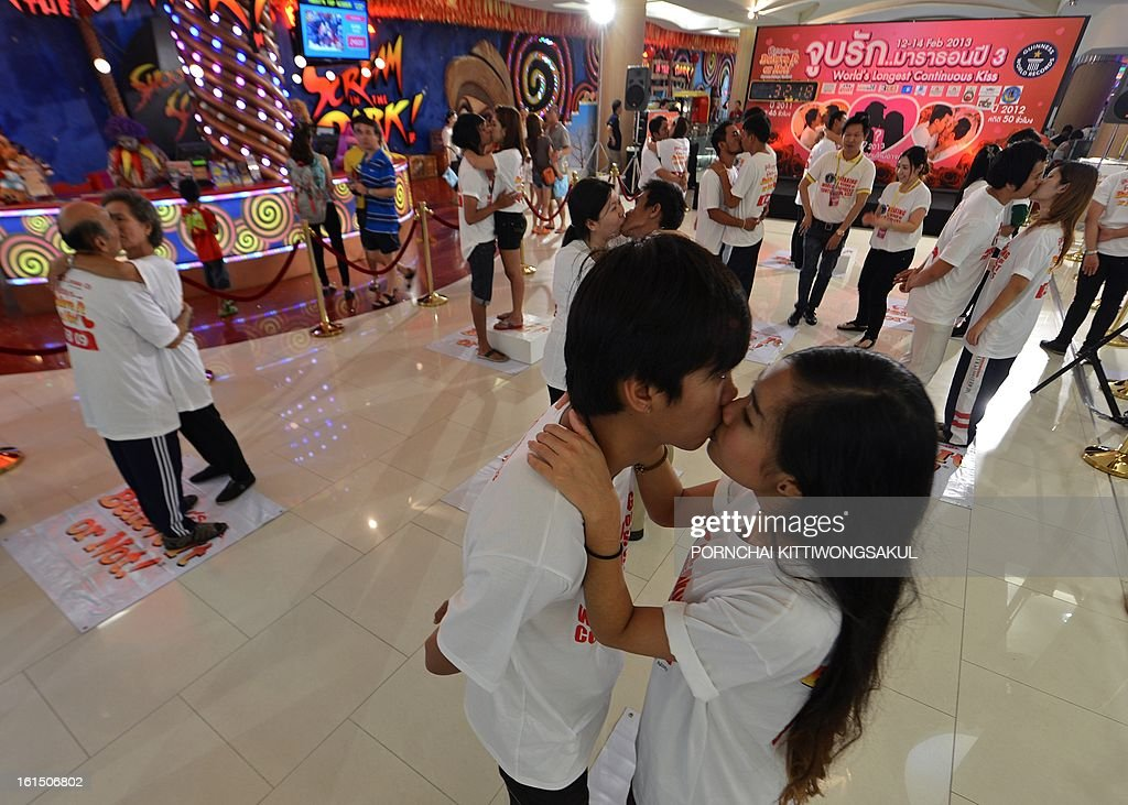 Thai couples kiss during a competition for the 'World's Longest Continous Kiss' ahead of Valentine's Day in Pattaya on February 12, 2013. Nine couples took part in the kissing marathon in the hope of breaking the Guinness world record, and in the process to receive prizes totalling more than 200,000 Thai baht (6,700 USD) and a diamond ring. AFP PHOTO/PORNCHAI KITTIWONGSAKUL