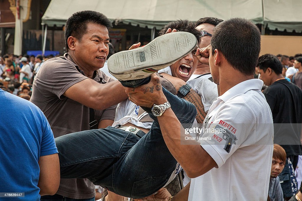 Thai devotee in state of trance is helped by volunteers during the celebration of the annual Tattoo festival at Wat Bang Phra on March 15 2014 in...