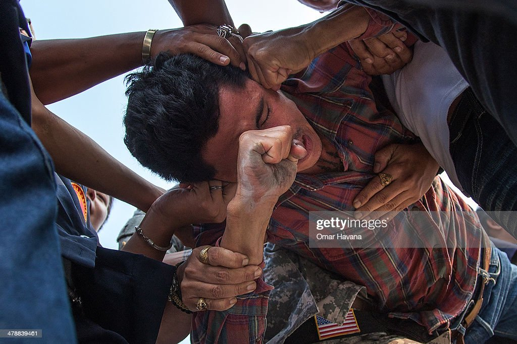 Thai devotee reportedly possessed by spirits is restrained by volunteers as he tries to pay his respects to a statue of Lord Buddha during the...