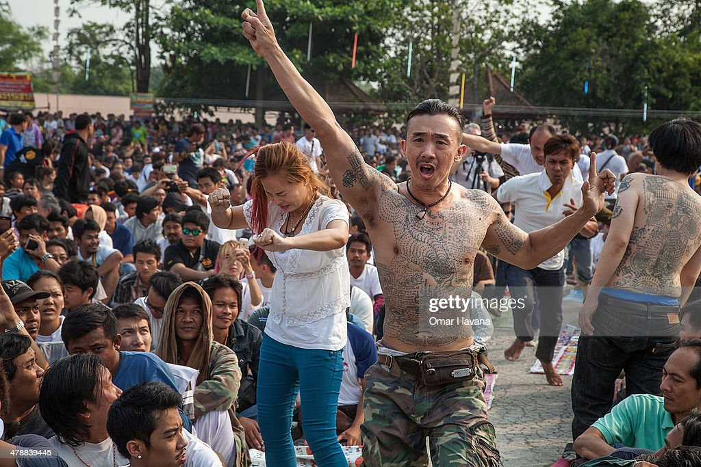 Thai devotees in state of trance run toward a statue of Lord Buddha to pay their respects during the celebration of the annual Tattoo festival at Wat...