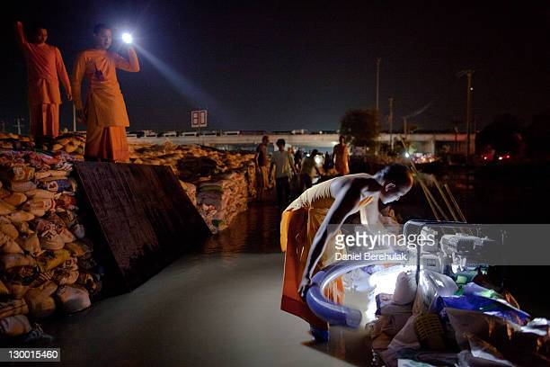 Thai Dhammakaya monk shines a light for a fellow monk working to repair a water pump as they and other volunteers work to fortify the flood gate and...
