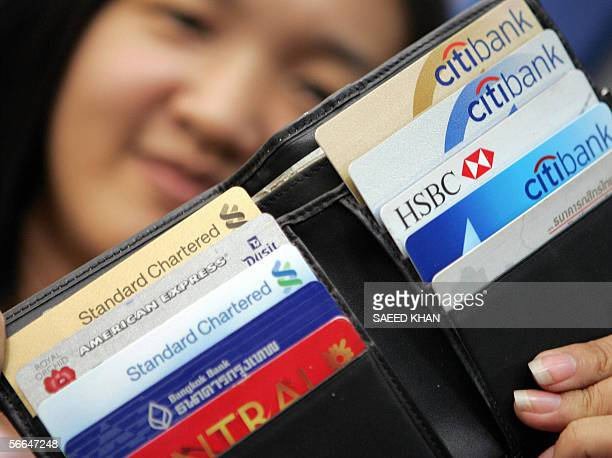 Thai employee shows a variety of credit cards in her wallet in downtown Bangkok 17 June 2005 Thais are on a shopping binge in the country's...