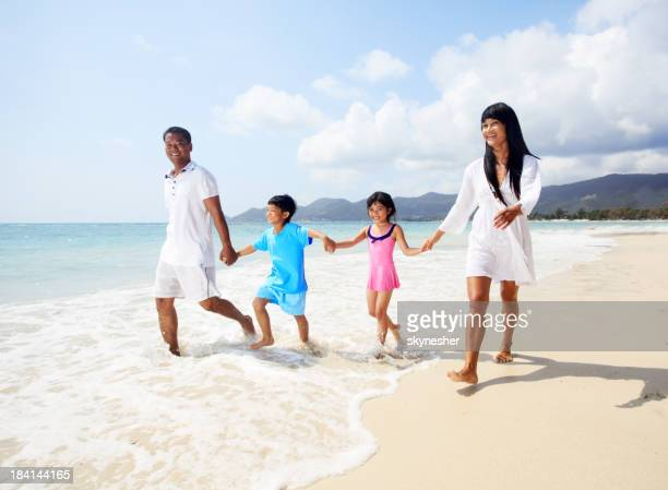 Thai family walking on the beach.
