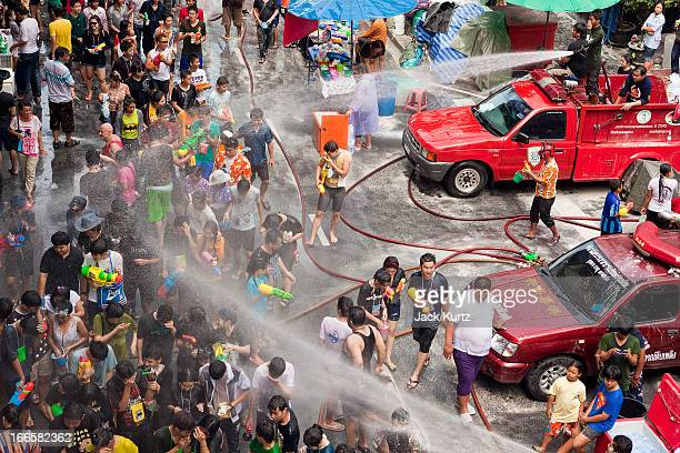 Thai fire fighters soak the crowd with their fire hoses during a community water fight on Silom Road as part of the Songkran water festival on April...