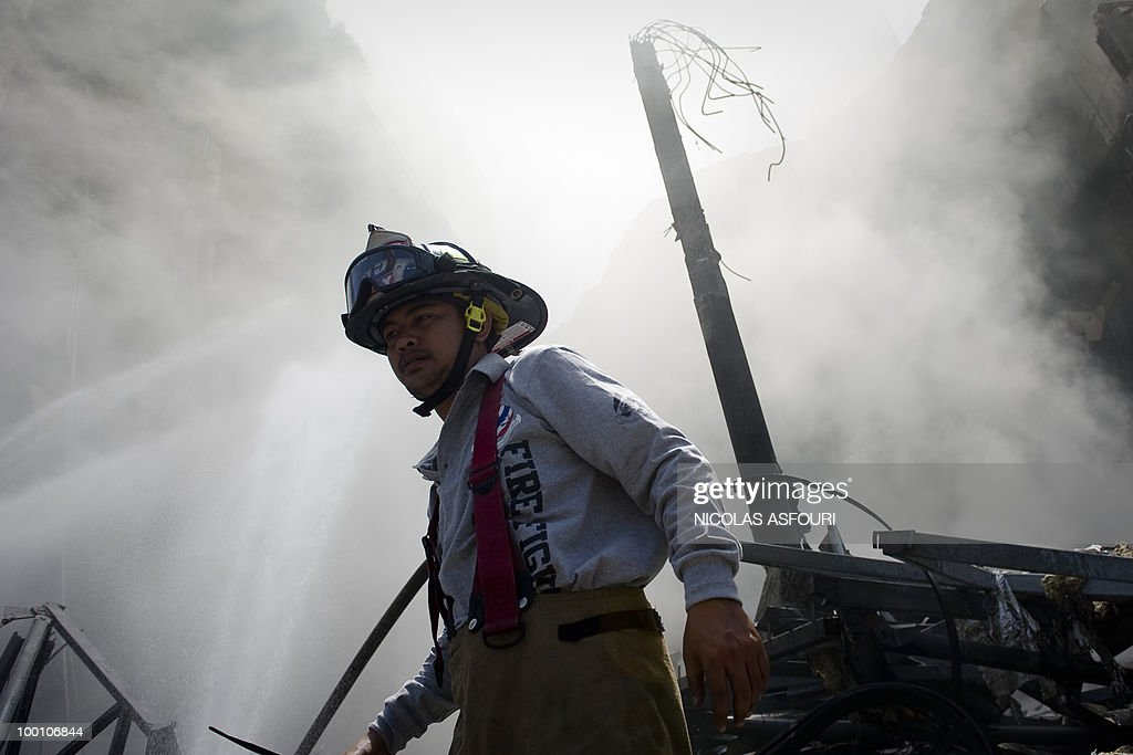Thai firemen continue to douse the smouldering remains of Thailand's biggest shopping mall - Central World - after it was set ablaze two days ago following an army assault on an anti-government protest site in downtown Bangkok on May 21, 2010. Thailand's biggest shopping mall faces collapse after it was set ablaze by enraged protesters in the wake of an army offensive to shut down an anti-government rally, police said. AFP PHOTO/ Nicolas ASFOURI