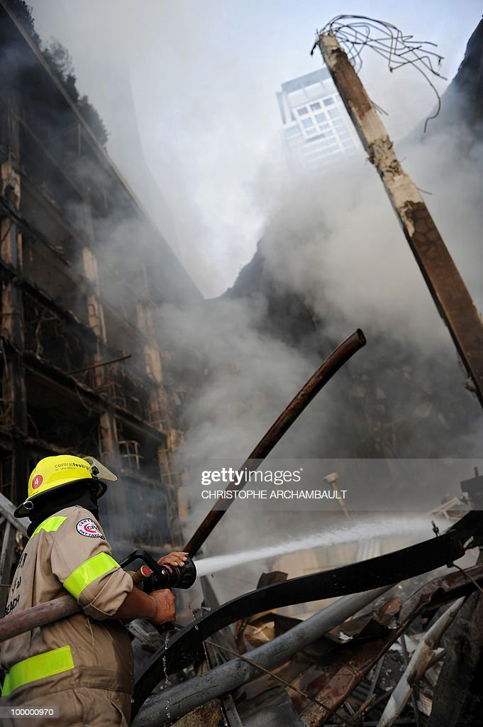 Thai firemen fight the fire at Thailand's biggest shopping mall - Central World - after it was set ablaze the day before following an army assault on an anti-government protest site in downtown Bangkok on May 20, 2010. Thailand's biggest shopping mall faces collapse after it was set ablaze by enraged protesters in the wake of an army offensive to shut down an anti-government rally, police said. AFP PHOTO/Christophe ARCHAMBAULT