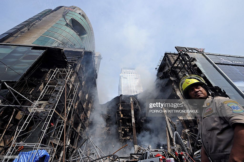 Thai firemen gather at the site of a fire at Thailand's biggest shopping mall - Central World - after it was set ablaze the day before following an army assault on an anti-government protest site in downtown Bangkok on May 20, 2010. Thailand's biggest shopping mall faces collapse after it was set ablaze by enraged protesters in the wake of an army offensive to shut down an anti-government rally, police said.