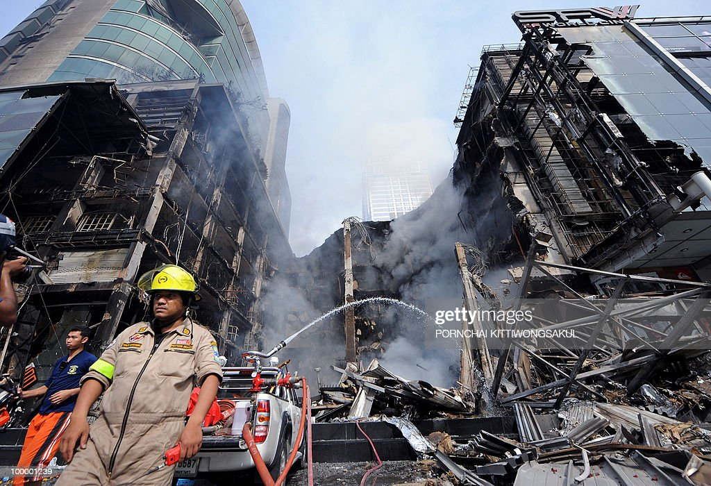 Thai firemen spray water on the smouldering site of a fire at Thailand's biggest shopping mall - Central World - after it was set ablaze the day before following an army assault on an anti-government protest site in downtown Bangkok on May 20, 2010. Thailand's biggest shopping mall faces collapse after it was set ablaze by enraged protesters in the wake of an army offensive to shut down an anti-government rally, police said.