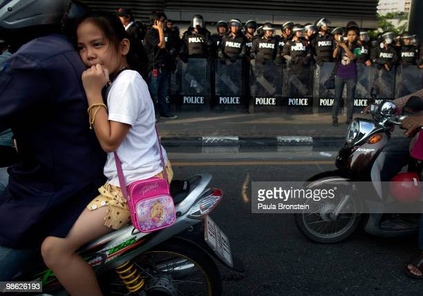 Thai girl is off to schol as Thai riot police stand guard across the street from the red shirt protesters anti government camp early morning as the...