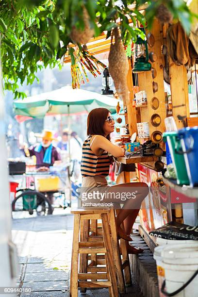 Thai girl sitting at street coffee booth