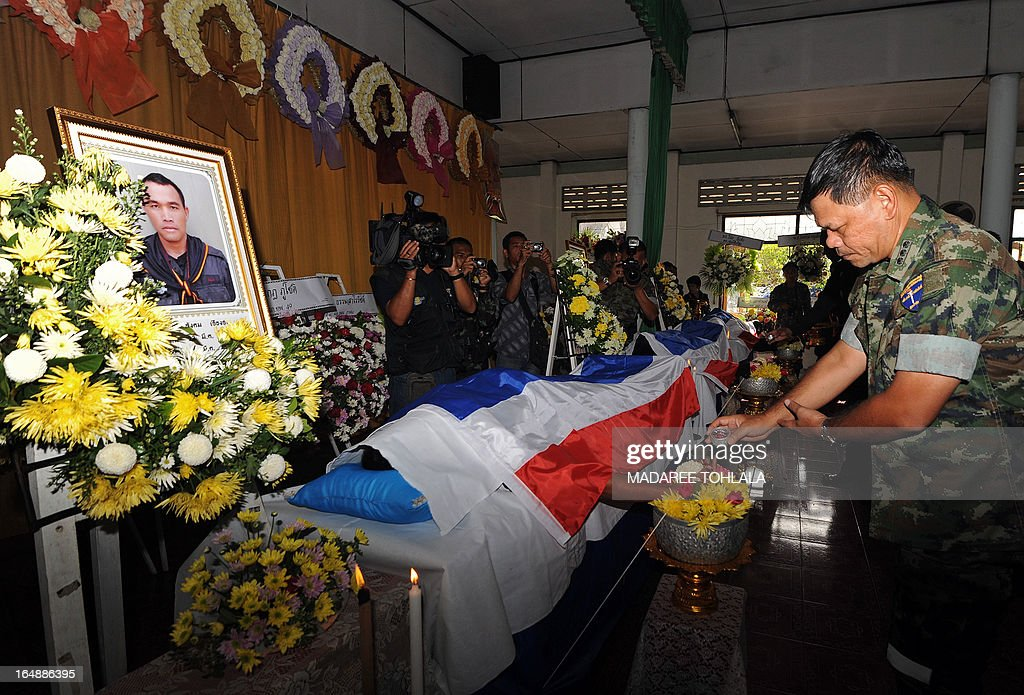 A Thai government official (R) performs Buddhist rites during the funeral ceremony of a ranger who was killed during a roadside bomb attack by suspected separatist militants a day before in Thailand's restive southern province of Narathiwat on March 29, 2013. Thailand held its first formal peace talks with a rebel group from its insurgency-racked south on March 28 as a bombing killed three people in a stark reminder of the difficulties negotiators face. AFP PHOTO/Madaree TOHLALA