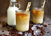 Thai iced coffee in a mason jar on a rustic wooden background.