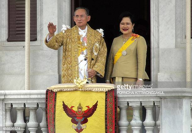 Thai King Bhumibol Adulyadej along with Queen Sirikit wave to thier people after his address in Bangkok 09 June 2006 Nearly one million Thais wearing...