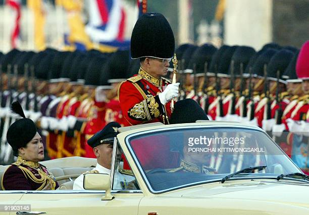 Thai King Bhumibol Adulyadej and Queen Sirikit review the troops as a part of the celebration to commemorate his 76th birthday at the royal plaza in...