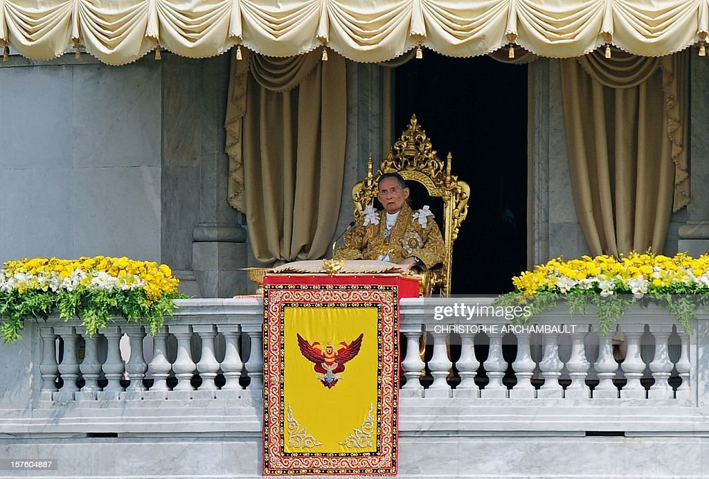 Thai King Bhumibol Adulyadej sits on a throne as he appears at a balcony of the Anantasamakom Throne Hall to deliver an address in front of the Royal Plaza in Bangkok's historic district on December 5, 2012. Tens of thousands of Thais crowded central Bangkok on December 5 for a rare address by King Bhumibol Adulyadej, the world's longest reigning monarch, as part of celebrations for his 85th birthday. AFP PHOTO/Christophe ARCHAMBAULT