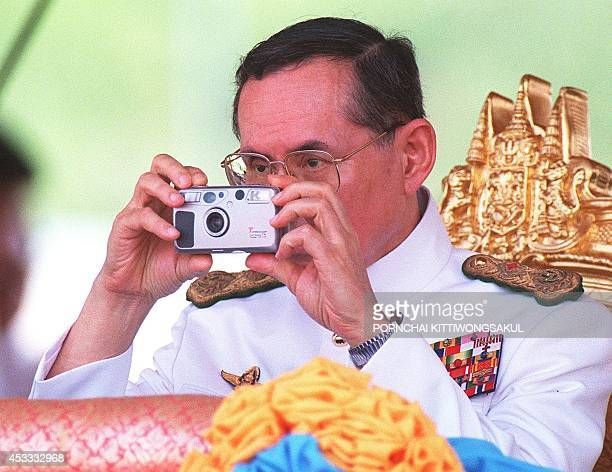 Thai King Bhumibol Adulyadej takes pictures 08 May during the royal ploughing ceremony in Bangkok The annual ceremony in which oxen plough a...
