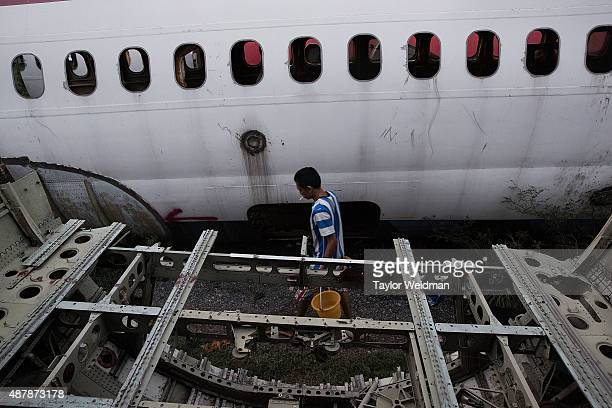 Thai man carries water to his home in a disused airplane on September 12 2015 in Bangkok Thailand 3 impoverished Thai families have begun living in...